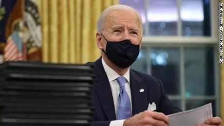 U.S. President Joe Biden prepares to sign a series of executive orders at the Resolute Desk in the Oval Office just hours after his inauguration on January 20, 2021.