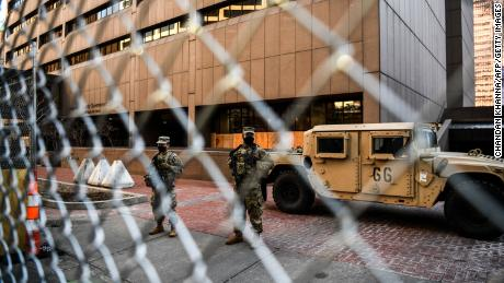 Members of the National Guard and Minnesota Police stand behind a barbed wire fence perimeter surrounding the Hennepin County Government Center in Minneapolis on Monday.